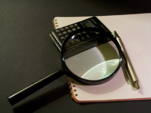 Image of magnifying class on a note pad with pen and calculator