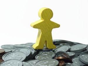 human-shaped cut out standing on coins