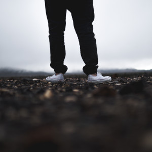 Image of person's feet outdoors, overcast sky in the background