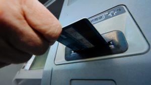 Image of hand inserting debit card into bank machine