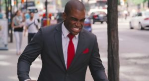 Picture of a man in a suit looking down in disgust