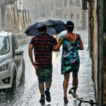 Man and women walking in the rain with an umbrella