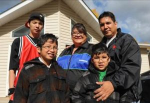 Aboriginal family standing outside of their home