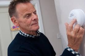 Man adjusting carbon monoxide detector in home
