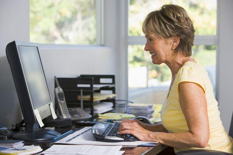 Woman typing on a desktop computer