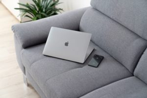 A laptop and phone sit on an empty couch.
