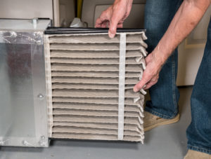 A man changes an HVAC filter.