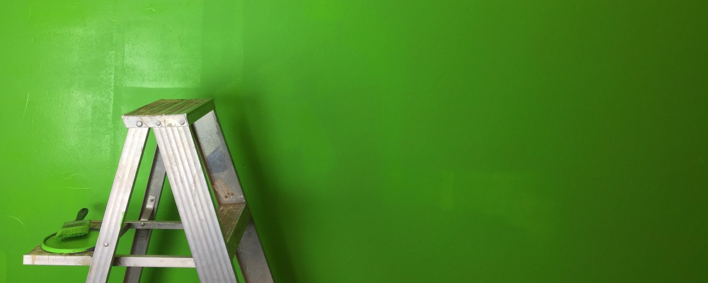 A ladder with a paint lid and brush sits against a freshly-painted wall.