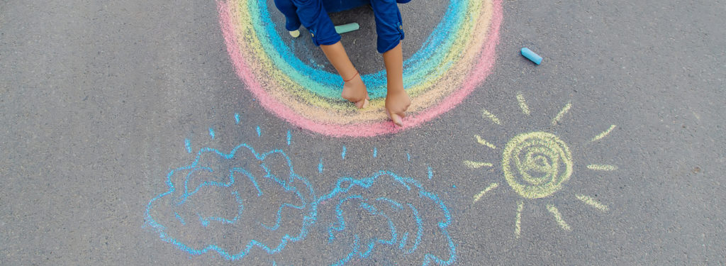A child draws a rainbow, sun and clouds on pavement.