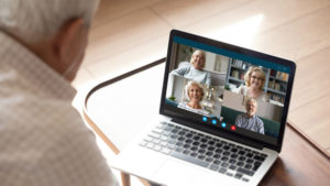 A male senior citizen using his laptop to video chat with four other senior citizens.