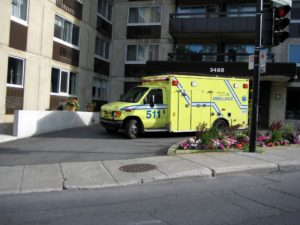 An ambulance sitting in the parking bay of an apartment building