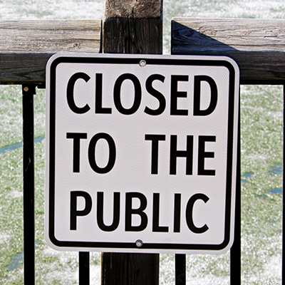 A sign on a fence that reads: closed to the public