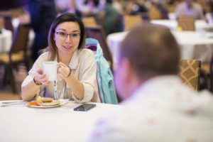 An ONPHA member sits with a cup of coffee, chatting with another ONPHA member across a table at the annual Conference.