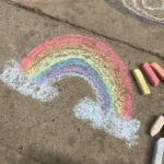 Sidewalk chalk art of a rainbow.