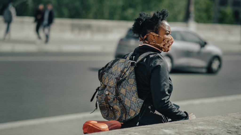 A woman wears a mask outside, walking her bicycle down the street.