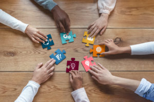 A diverse group of individuals' hands putting puzzle pieces together symbolizing different actions and strategic planning