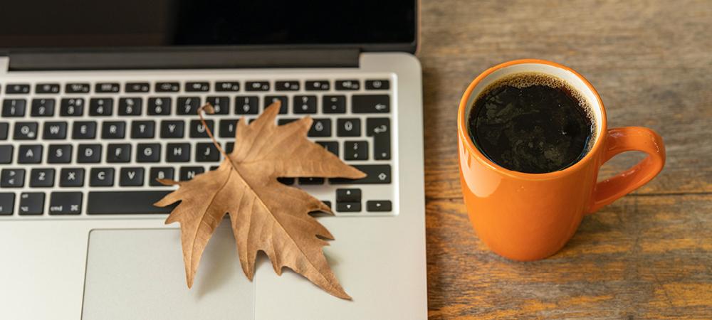 A fall leaf sitting on a laptop keyboard with an orange coffee mug alongside.