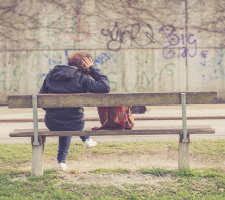 Back view of  a woman sitting alone on a park bench