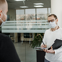 A man wearing a medical mask writes on a clipboard while talking to another man wearing a medical mask