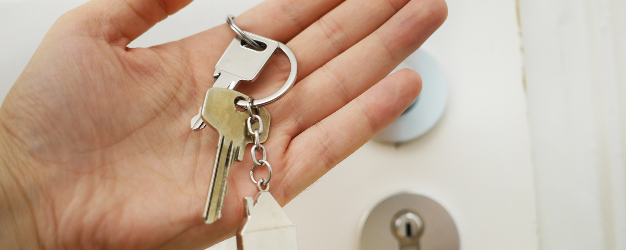 A hand holds a set of apartment keys.