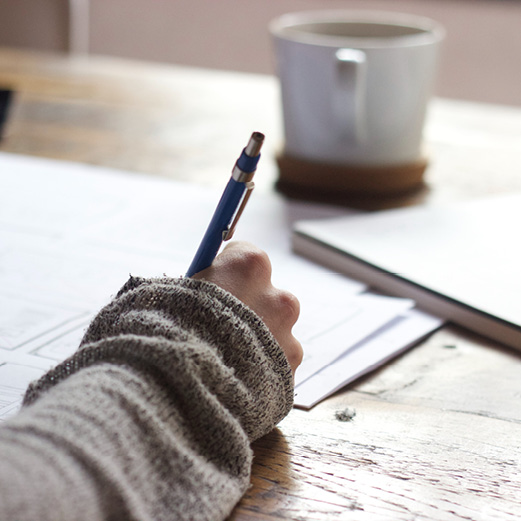 Close up of a woman's hand writing with a pen