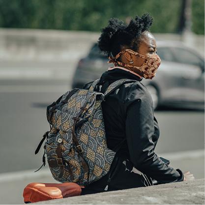 A woman wearing a mask walks a bike down the street.