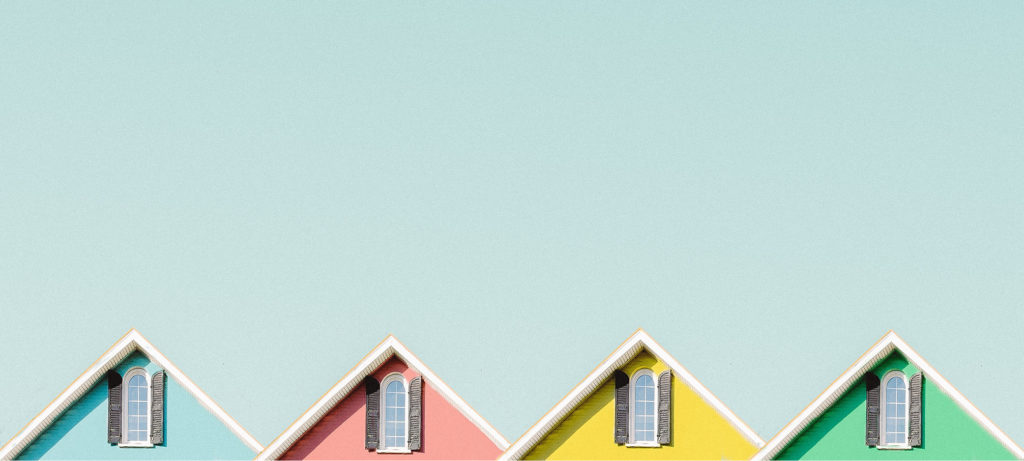 The tops of a row of brightly-coloured houses sit against a light blue background.