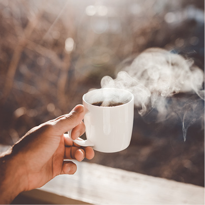 A man's hand holding a cup of coffee on an outdoor balcony or deck.