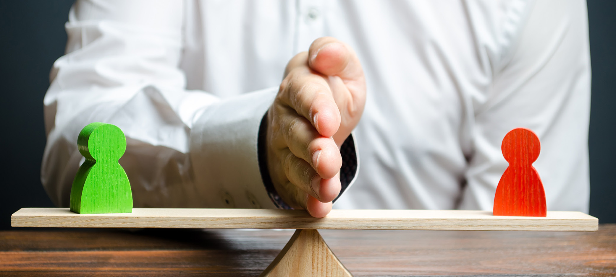 Two wooden figures balance on a scale. A man's hand is put up as a divider between them.