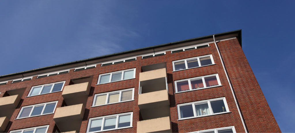 View from the ground up of an apartment building against a blue sky.