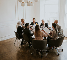 A group of people sit in discussion around a meeting table