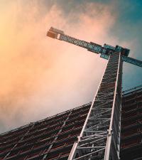 A crane sits beside a building under construction.