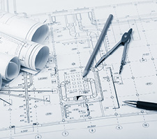 Blueprints sit on a table with pens and a protractor.