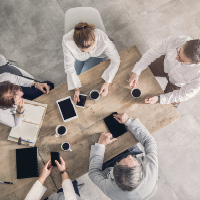 A group of people work around a boardroom table.
