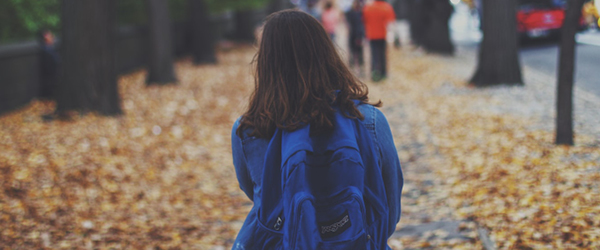 Young girl with a blue backpack walking to school